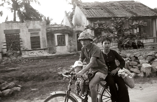 Hai vợ chống và đứa con đạp xe qua một khu dân cư bị Mỹ ném bom. 1965.