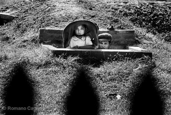 Bé gái và cha lấp ló bên miệng hầm trú ẩn.