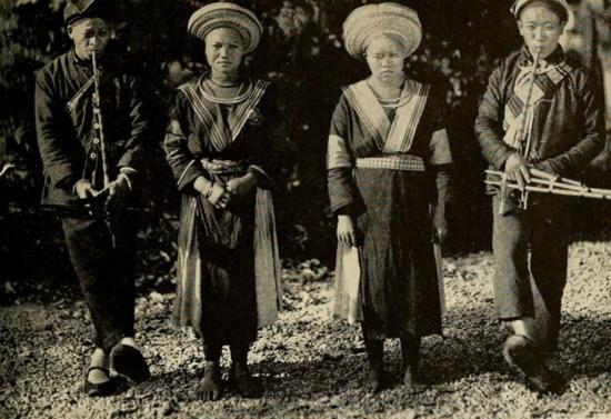Hai chàng trai H'Mông chơi khèn bên hai sơn nữ H'Mông ở Cao Bằng.