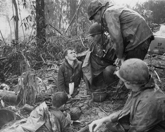 Một thương binh Mỹ nói chuyện với cha tuyên úy, bên cạnh là các đồng đội bị thương đang chờ di tản khỏi Đồi Thịt Băm, 20/5/1969.