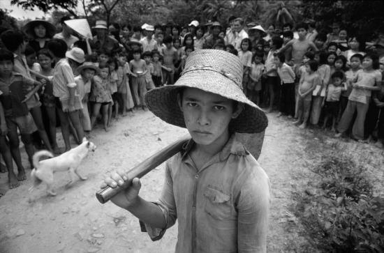 """Cu Tèo sống với bố mẹ nuôi của mình là ông Trần Văn Bảo và bà Trần Thị Hằng trên mảnh đất nhỏ cách phía Bắc của Bến Tre khoảng 10 km. Em đã bỏ học để làm ruộng như mọi người nông dân khác trong vùng vì thường bị bạn bè trong lớp trêu chọc về nguồn gốc con lai của mình. Cu Tèo bị mẹ bỏ rơi trong một khu rừng khi di tản khỏi Kontum trong những ngày cuối cùng của cuộc chiến tranh Việt Nam vào năm 1975, khi đó em mới 5 tuổi.  Sau chiến tranh, một số người đã ngỏ ý muốn """"mua"""" cậu bé Việt lai Mỹ này, nhưng đều đã bị từ chối. Khi gặp phóng viên, Cu Tèo đã bỏ chạy, và chỉ bình tĩnh lại khi biết rằng người đàn ông lạ mặt đến đây không phải để bắt mình đi."""