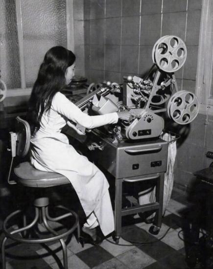 Một kỹ thuật viên nữ đang kiểm tra các đoạn phim 35mm Sound Moviola ở phòng chế bản của đài truyền hình Sài Gòn trước khi chuyển đổi về định dạng phim 16mm và tiến hành lồng âm, ngày 23/1/1967.