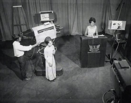 Hai nữ dẫn chương trình sẵn sàng cho buổi ghi hình chương trình thời sự hàng ngày tại phim trường trong lúc một người quay phim kiểm tra lại thiết bị lần cuối.