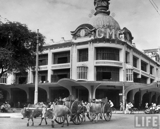 Xe bò kéo chạy qua tòa nhà sau này trở thành thương xá Tax ở Sài Gòn.