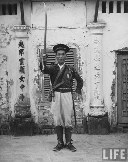 Người lính Việt Nam phục vụ chính quyền Pháp tên Trần Đăng Mẫn thực hiện một nghi thức nhà binh.