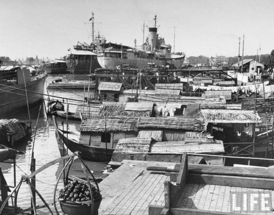 Tàu vận tải Pháp đậu gần những con thuyền lụp xụp của người Việt trên sông Sài Gòn.