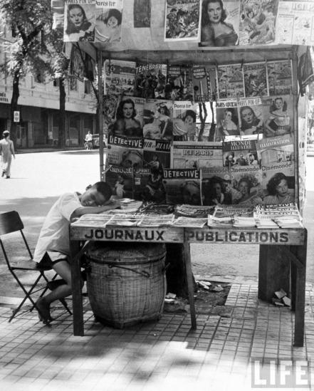 Cậu bé bán báo ngủ gục bên quầy bán báo tiếng Pháp ở Sài Gòn.
