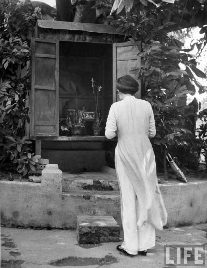Người phụ nữ thắp hương tại một am thờ, Hà Nội.