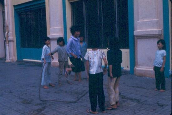 Những đứa trẻ nhảy dây trên vỉa hè.