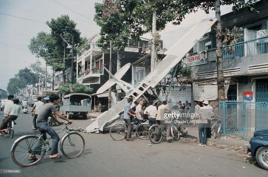 Hiện trường vụ máy bay rơi ở Sài Gòn năm 1975 trong ảnh của Jean-Claude Labbe. Dù rơi giữa trung tâm thành phố nhưng chiếc máy bay không gây thương vong cho dân thường do kích cỡ nhỏ và không xảy ra cháy nổ khi rơi.