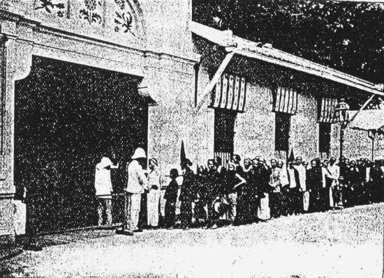 Công nhân tan ca ra về tại cổng sau của nhà máy.