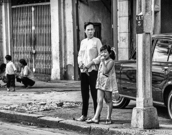 Bé gái cười tươi khi đứng cùng mẹ bên vỉa hè.