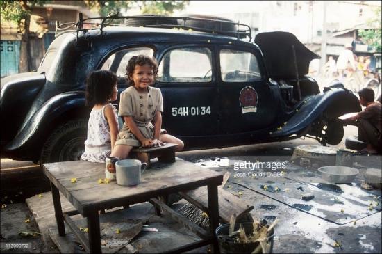 Những đứa trẻ bên chiếc taxi có từ thời Pháp đang được tân trang.