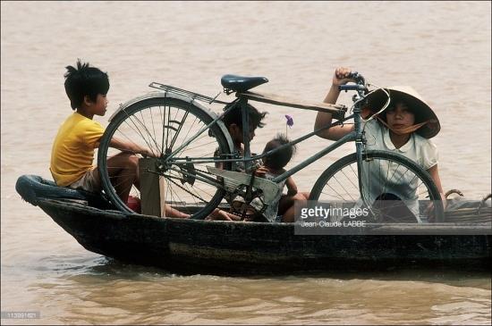 Người mẹ và những đứa con nhỏ cùng chiếc xe đạp qua sông trên một chuyến đò.