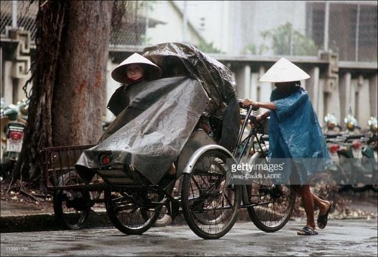 Người lái xích lô hành nghề dưới mưa.