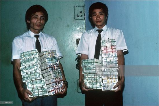Hai nhân viên Ngân hàng Thành phố cầm trên tay các chồng tiền Việt Nam đồng và đô-la Mỹ.