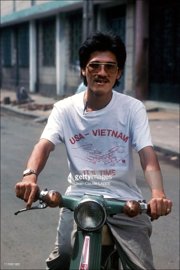 """Người đàn ông mặc chiếc áo in dòng chữ tiếng Anh: """"Mỹ - Việt Nam, đã đến lúc"""". Khoảng 4 năm sau khi bức ảnh này được chụp quan hệ Việt - Mỹ đã chính thức được bình thường hóa."""