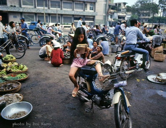 Bé gái đọc sách trong lúc chờ mẹ mua hàng ở chợ, 1990.