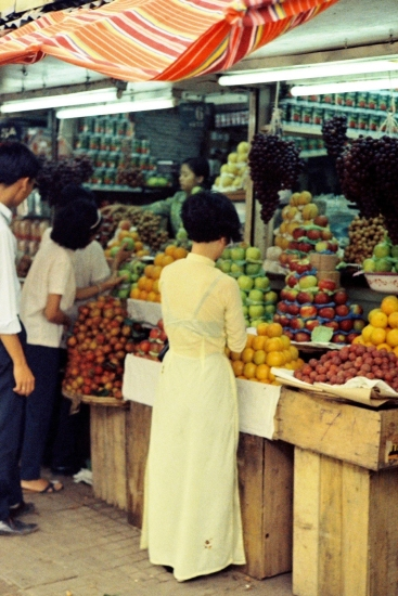 Thiếu nữ áo dài chọn mua hoa quả.