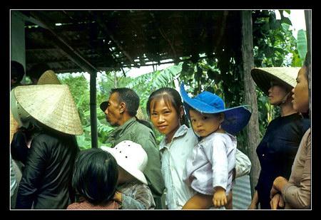 Chú thích của Steve Brown trên Flickr cá nhân của mình về bức ảnh: Một người mẹ (hay chị?) mẹ và em bé có cái mũ khá sành điệu.