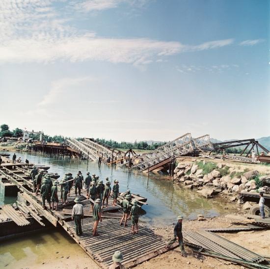 Một cầu tạm đang được dựng cạnh một cây cầu bị bom Mỹ đánh sập.