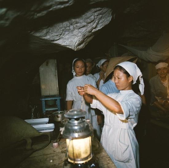 Các nhân viên y tế chăm sóc bệnh nhân dưới ánh sáng của đèn dầu.