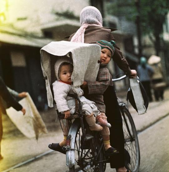 Hai em bé được mẹ chở bằng xe đạp trên phố.