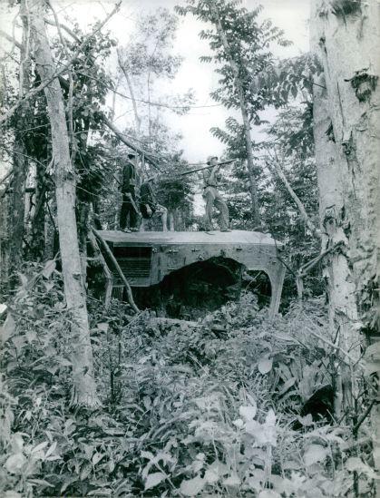 Các chiến sĩ du kích đứng trên xác một khí tài quân sự Mỹ trong rừng, 1967.