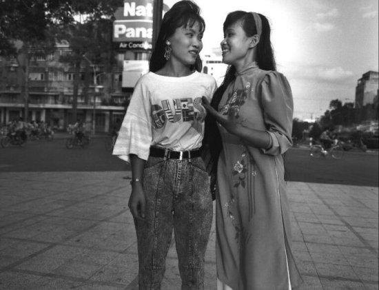 Hai thiếu nữ, một người mặc áo dài truyền thống, người kia mặc quần bò áo phông tán gẫu trên đường phố ở TP HCM.