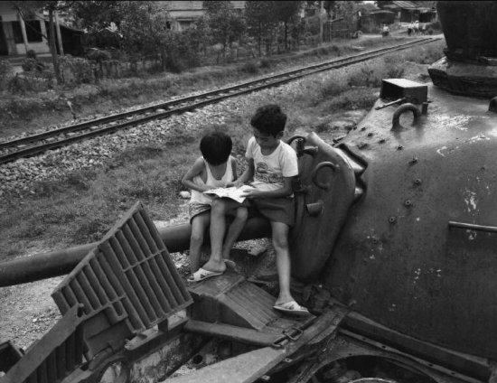 Trẻ em ngồi đọc sách trên xác một chiếc xe tăng ở Đông Hà, Quảng Trị.
