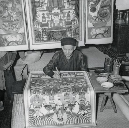 """Nghệ nhân tranh Hàng Trống tô màu lên bức tranh """"Tứ Phủ"""", Hà Nội năm 1953."""