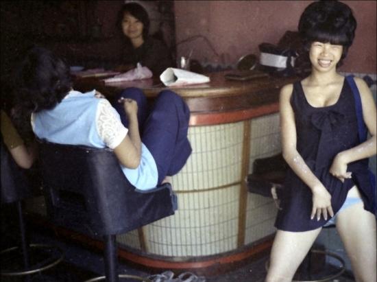 Một cô gái điếm khoe thân mời chào khách trong quán bar ở Vũng Tàu năm 1970. Ảnh: Laurie Smith