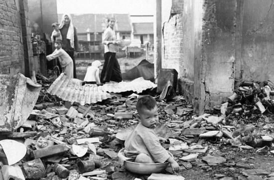 Một em bé ngồi trong khu đổ nát khi cha mẹ em tìm kiếm những gì còn sót lại của ngôi nhà bị phá hủy. Tấm ảnh này chụp ở Cholen ngày 10/5/1955.