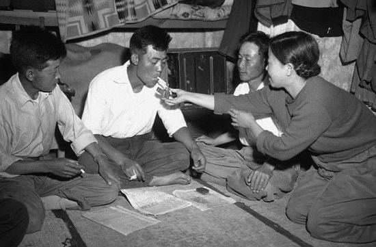 Một phụ nữ Hàn Quốc châm lửa cho một trong những tù nhân chiến tranh Triều Tiên đào thoát khỏi đất nước. Nhiếp ảnh gia Waters đã chụp tấm ảnh này vào ngày 26/6/1953.