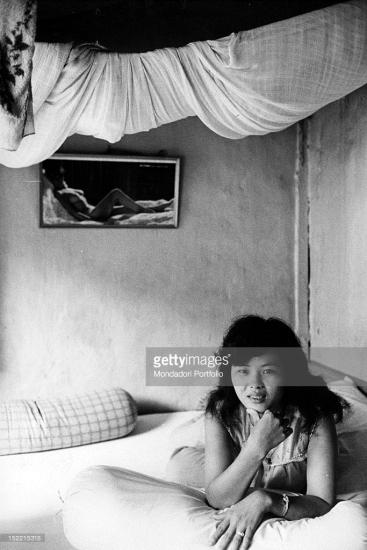 """Cô gái này chuẩn bị """"tiếp khách"""" trên chiếc giường trong một căn phòng tồi tàn, Sài Gòn tháng 1/1968. Ảnh: Getty Images. Ảnh: Mondatori."""