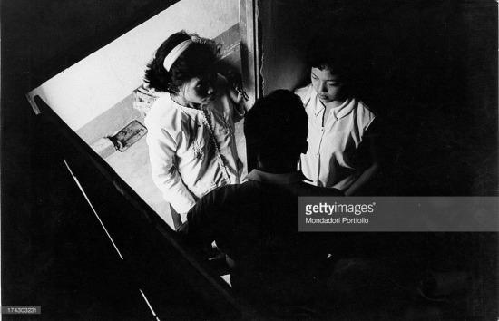 """Cuộc trao đổi kín đáo giữa người lính Mỹ và hai cô gái """"bán hoa"""". Ảnh: Mondatori"""