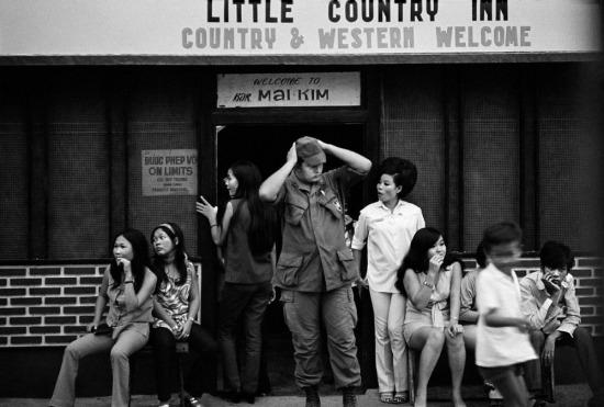 Bên ngoài quán bar Mai Kim ở Cần Thơ, 1970. Phía sau các quán bar phục vụ lính Mỹ là sự bảo kê từ giới chức quân đội Sài Gòn. Ảnh: Philip Jones Griffiths.
