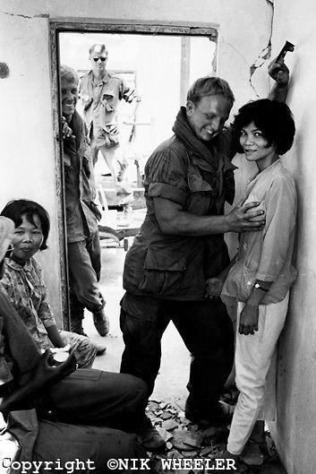 Lính Mỹ đùa giỡn với gái điếm trong một tòa nhà đổ nát ở ngoại ô Sài Gòn. Ảnh: Nik Wheeler.